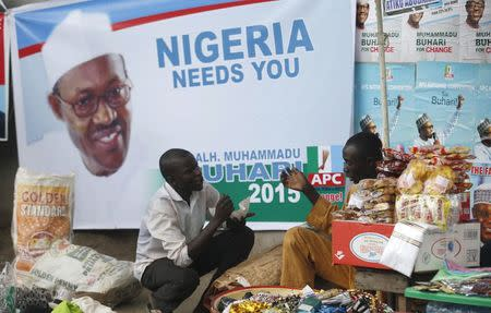 Vendors sell their wares near an election poster of former Nigerian military ruler Muhammadu Buhari in Lagos