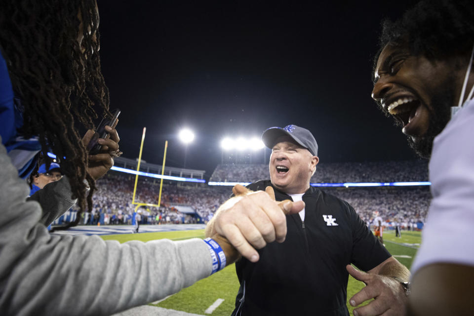 Kentucky head coach Mark Stoops, center, slaps hands with rapper Waka Flocka Flame, left, after winning an NCAA college football game against Florida in Lexington, Ky., Saturday, Oct. 2, 2021. (AP Photo/Michael Clubb)