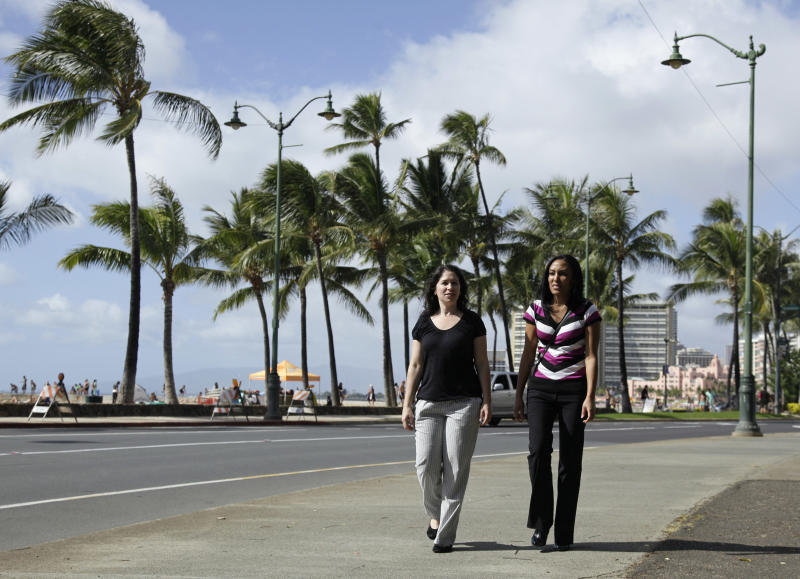 FILE - In this Dec. 19, 2011 file photo, Diane Cervelli, left, and Taeko Bufford, right, and walk past Waikiki beach in Honolulu. A Hawaii First Circuit Court judge ruled in favor of the Southern California couple who sued Aloha Bed & Breakfast for discrimination in 2011, Lambda Legal announced Monday, April 15, 2013. In 2007, Diane Cervelli and Taeko Bufford tried to book a room at the bed and breakfast because it's in Hawaii Kai, the same east Honolulu neighborhood where the friend they were visiting lived. (AP Photo/Eric Risberg, File)