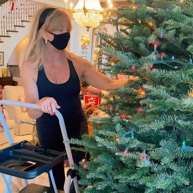<p>The actress masks up and gets to work putting the finishing touches on her tree (though she lowers it to blow a kiss at the end). </p>