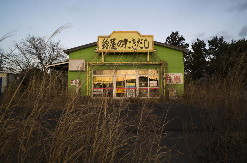 An abandoned restaurant stands surrounded by weeds in the exclusion zone in Tomioka town, Fukushima prefecture, northeastern Japan, Saturday, Feb. 27, 2021. The no-go zone sits on its northeastern corner within about 10 kilometers (6 miles) of the wrecked Fukushima Daiichi nuclear power plant where massive radioactive fallouts spewed in 2011. (AP Photo/Hiro Komae)