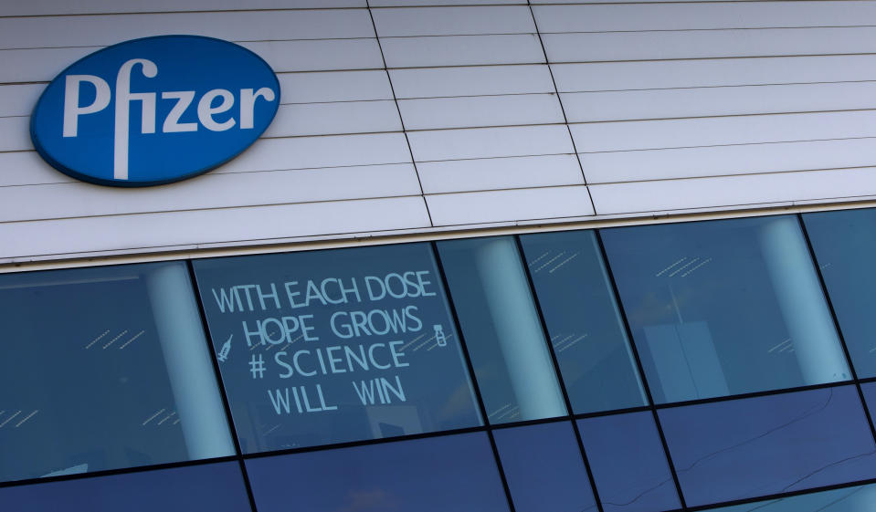 FILE - In this Tuesday, Feb. 23, 2021 file photo, a sign is pasted into an upper window at Pfizer manufacturing center in Puurs, Belgium. The European Union cemented its support for Pfizer-BioNTech and its novel COVID-19 vaccine technology, Saturday, May 8, 2021 by agreeing to a massive contract extension for a potential 1.8 billion doses through 2023. The new contract, which has the backing of the EU member states, will entail not only the production of the vaccines, but also making sure that all the essential components should be sourced from the EU. (AP Photo/Virginia Mayo, File)