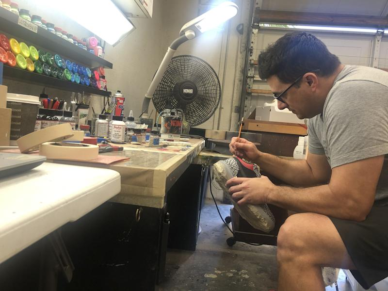 Padron works on a pair of Air Jordans, applying the famous elephant print.