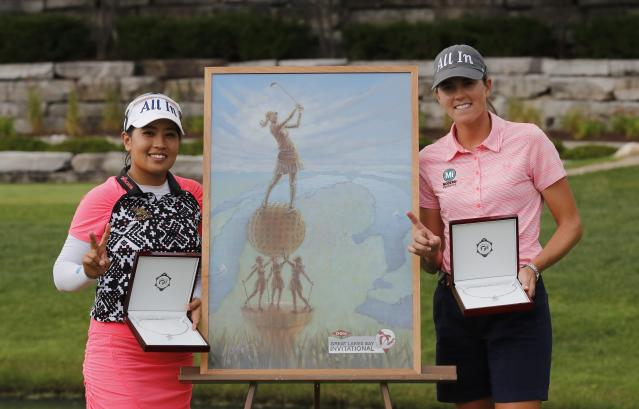 Jasmine Suwannapura of Thailand, left, and teammate Cydney Clanton pose with the winner's trophy, a painting, on the 18th green during the final round of the Dow Great Lakes Bay Invitational golf tournament, Saturday, July 20, 2019, in Midland, Mich. (AP Photo/Carlos Osorio)