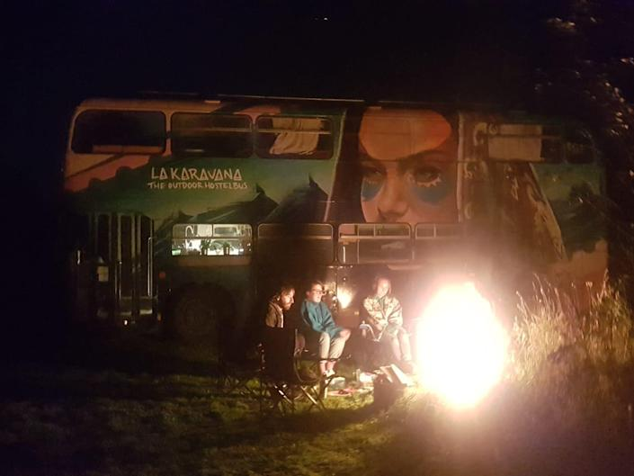 a group of people around a campfire with the double decker bus in the background
