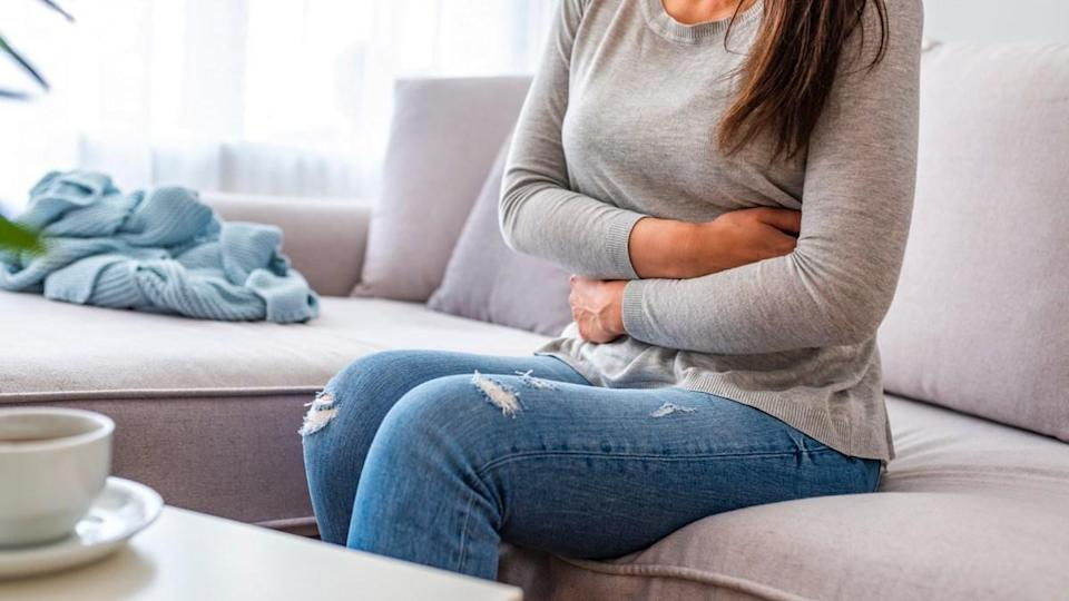 woman with stomach ache sitting on sofa