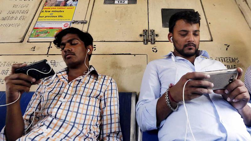 Commuters watch videos on their mobile phones as they travel. Reuters