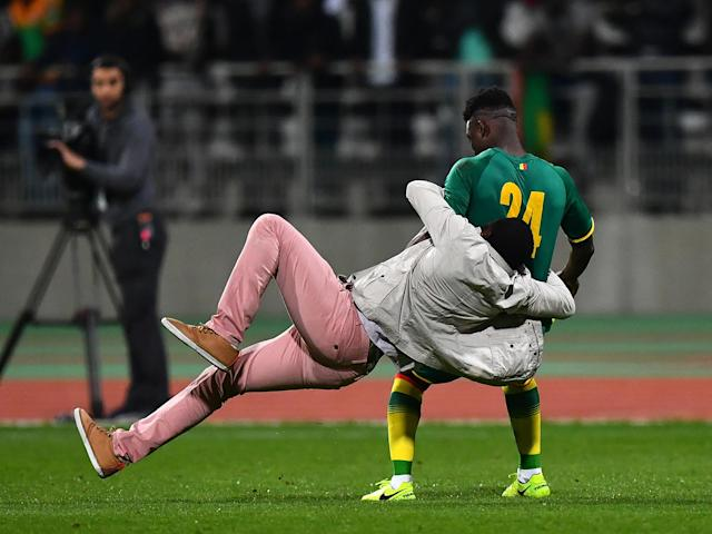 A pitch invader tackles Lamine Gassama of Senegal: Getty