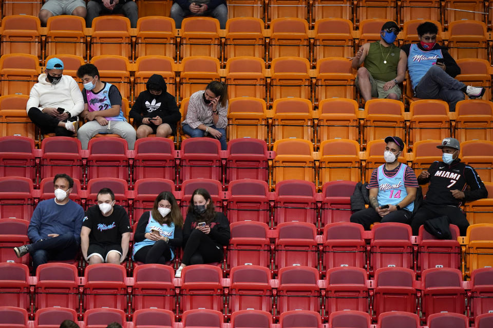 Blocks of two to four fans sit staggered in different rows of seats while wearing masks.