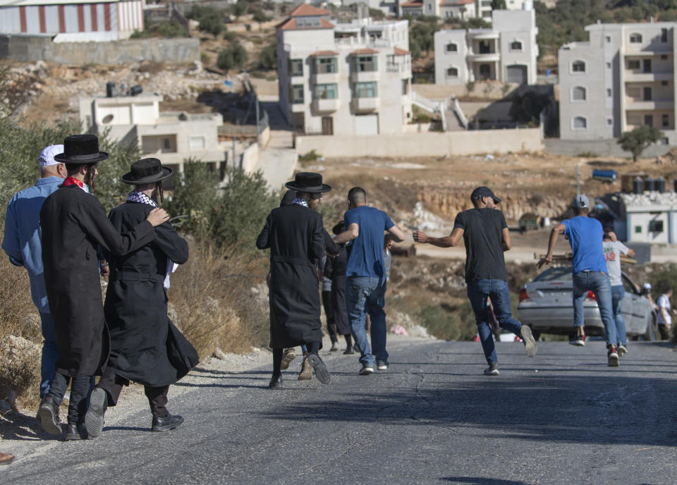 Members of the ultra Orthodox Neturei Karta group and activists run for cover as Israeli border police dispersed activists trying to join Palestinian farmers and help them reach their groves for olive harvest, in the West Bank village of Burqa, East of Ramallah, Friday, Oct. 16, 2020. Palestinians clashed with Israeli border police in the West Bank on Friday during their attempt to reach and harvest their olive groves near a Jewish settlers outpost. (AP Photo/Nasser Nasser)