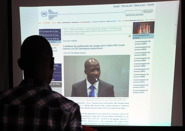 A member of the 'Young Patriots', a fanatical group supporting former Ivory Coast president Laurent Gbagbo, looks at a projection of an article related to the court proceedings of Charles Ble Goude on October 2, 2014, in Abidjan (AFP Photo/Sia Kambou)