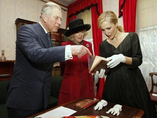 US actress Gillian Anderson (R) shows a first edition of a book by British novelist Charles Dickens, with the author's annotations, to Britain's Prince Charles (L) and his wife Camilla (C), Duchess of Cornwall, during a tour of the Dickens Museum in London on Tuesday as Britain marked the 200th anniversary of the writer's birth
