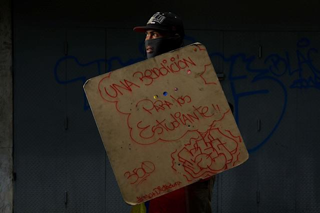 "<p>A demonstrator holding a rudimentary shield that reads ""A benediction for the students"", poses for a picture before a rally against Venezuelan President Nicolas Maduro's government in Caracas, Venezuela, May 24, 2017. He said: ""I am in the streets resisting because in this country we are living in a dictatorship and we want to have a better future for our children. Because food is not available, there are no jobs, no production of anything, we have high cost of living and insecurity."" (Photo: Carlos Garcia Rawlins/Reuters) </p>"