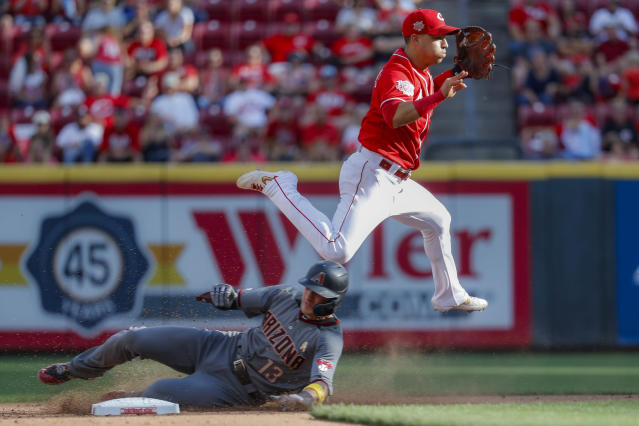 Cincinnati Reds shortstop Jose Iglesias, right, leaps over Arizona Diamondbacks' Nick Ahmed after turning a double play in the seventh inning of a baseball game, Saturday, Sept. 7, 2019, in Cincinnati. (AP Photo/John Minchillo)