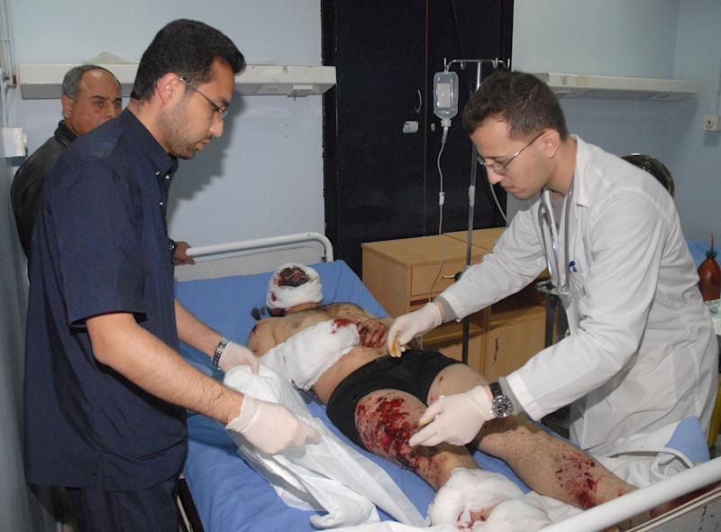 In this photo released by the Syrian official news agency SANA, Syrian doctors treat an injured man who was wounded at the Eman Mosque where a suicide bomber blew himself up, killing Sheikh Mohammad Said Ramadan al-Buti, an 84-year-old cleric known to all Syrians as a religious scholar, at the Mazraa district, in Damascus, Syria, Thursday, March 21, 2013. A suicide bomber blew himself up during evening prayers inside a mosque in Damascus Thursday, killing a top Sunni Muslim preacher and longtime supporter of President Bashar Assad and least 13 other people, state TV reported. Al-Buti's death is a big blow to Syria's embattled leader, who is fighting mainly Sunni rebels seeking his ouster. (AP Photo/SANA)