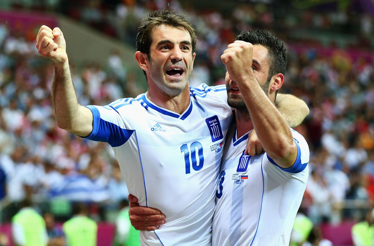 WARSAW, POLAND - JUNE 16:  Giorgos Karagounis and Giorgos Tzavelas of Greece celebrate victory and progress to the quarter finals during the UEFA EURO 2012 group A match between Greece and Russia at The National Stadium on June 16, 2012 in Warsaw, Poland.  (Photo by Shaun Botterill/Getty Images)