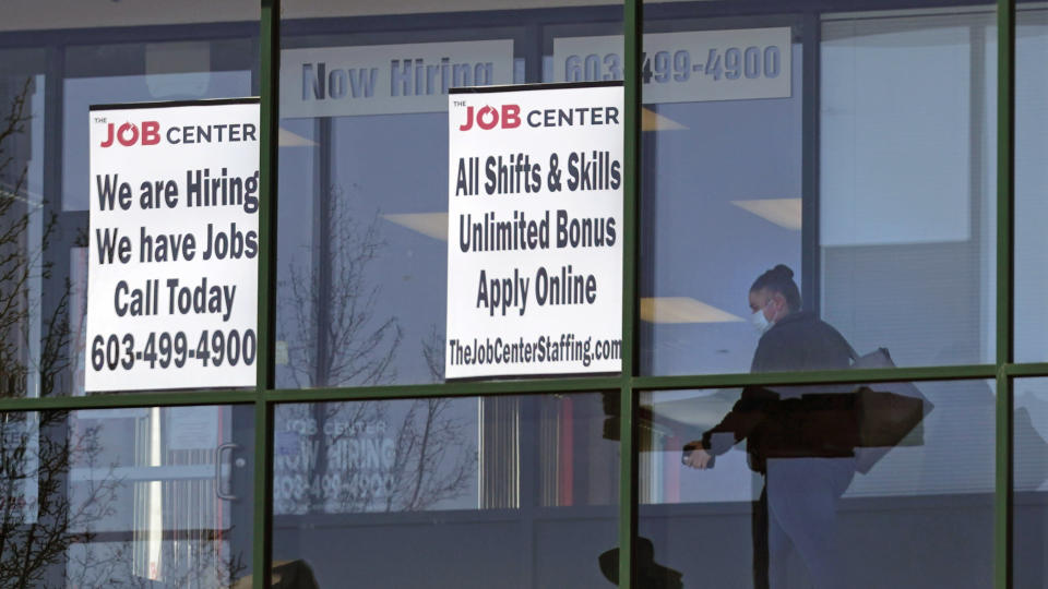 A woman, wearing a protective mask due to the COVID-19 virus outbreak, walks past the signs of an employment agency, Tuesday, March 2, 2021, in Manchester, N.H. After a year of ghostly airports, empty sports stadiums and constant Zoom meetings, growing evidence suggests that the economy is strengthening. Hiring picked up in February 2021. Business restrictions have eased as the pace of viral infections has ebbed. Yet the economy remains far from normal. (AP Photo/Charles Krupa)