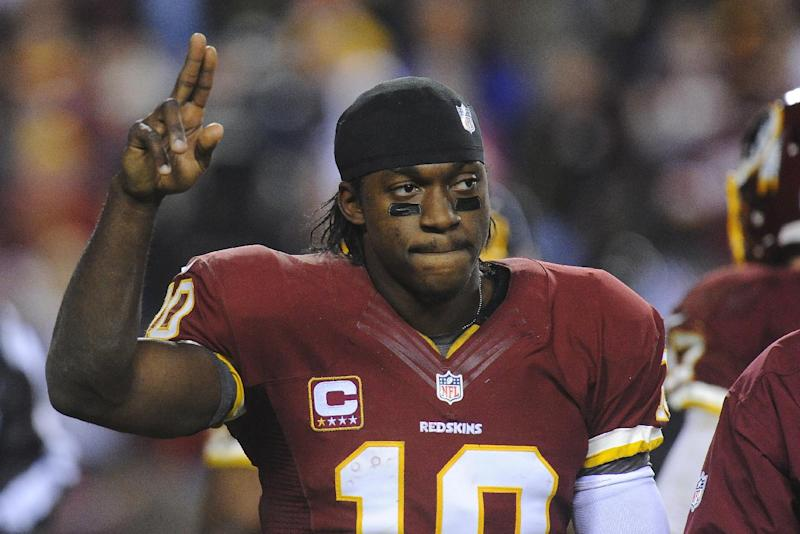 Washington Redskins quarterback Robert Griffin III salutes the crowd as he walks off the field with a twisted knee during the second half of an NFL wild card playoff football game against the Seattle Seahawks in Landover, Md., Sunday, Jan. 6, 2013. The Seahawks defeated the Redskins 24-14. (AP Photo/Richard Lipski)