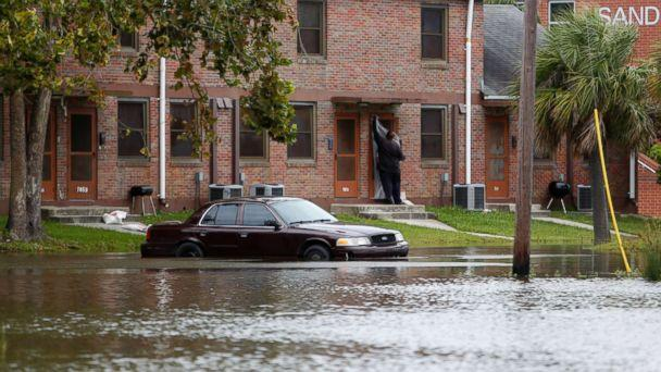 PHOTO: A Charleston, S.C. resident puts plastic up over his apartment door as a car rests in floodwaters near East Bay Street in Charleston, S.C., Sept. 10, 2017. (Mic Smith/AP)