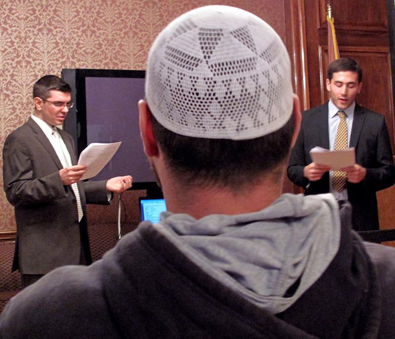 In this Oct. 26, 2011, photo, Joseph Ramagli, left and Robin Gordon-Leavitt, law students at the City University of New York, teach a group of Muslims in the Brooklyn borough of New York how to identify a police informant. They were acting out an actual  transcript of a recorded conversation between a police informant and his target. in the Brooklyn borough of New York, teach them about their rights in regard to an NYPD surveillance program targeting Muslims.  Fed up with a decade of the police spying on the innocuous details of the daily lives of Muslims, activists in New York are discouraging people from going directly to police with concerns about terrorism, a campaign that is certain to further strain relations between the two groups. Muslim community leaders are openly teaching people how to identify police informants, encouraging them to always talk to an attorney before speaking with authorities and reminding people already working with law enforcement that they have the right to change their minds.  (AP Photo/Chris Hawley)