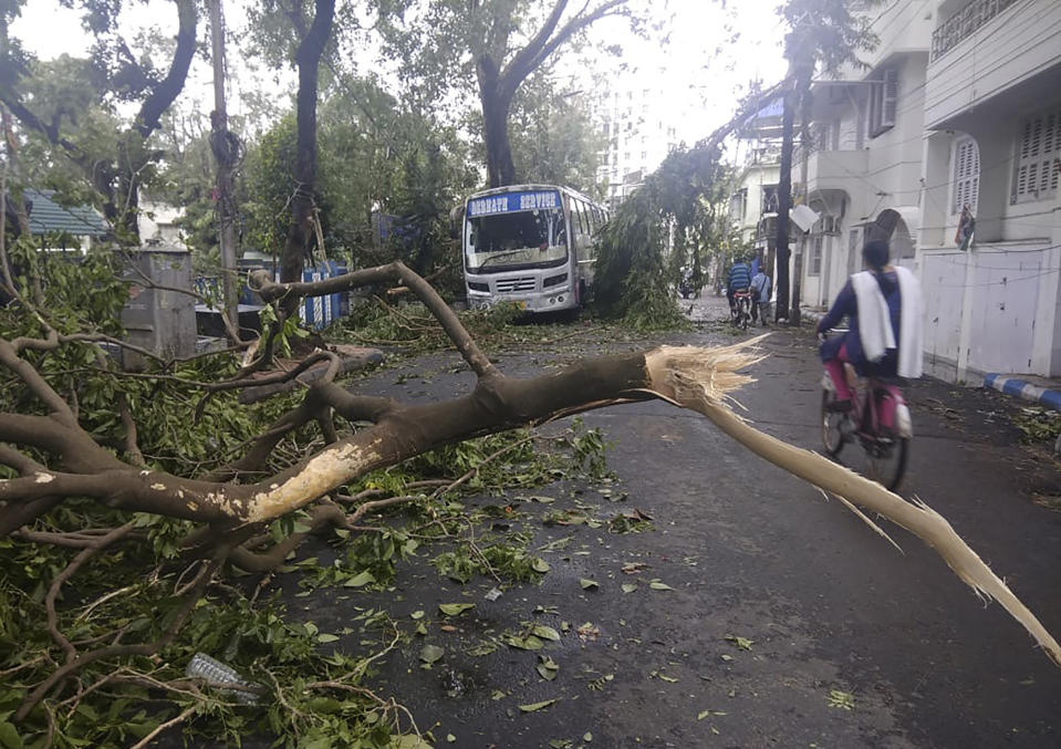 A girl rides a cycle past tree branches that fell after cyclone Amphan hit the region, in Kolkata, India, Thursday, May 21, 2020. A powerful cyclone that slammed into coastal India and Bangladesh has left damage difficult to assess Thursday. (AP Photo/Bikas Das)
