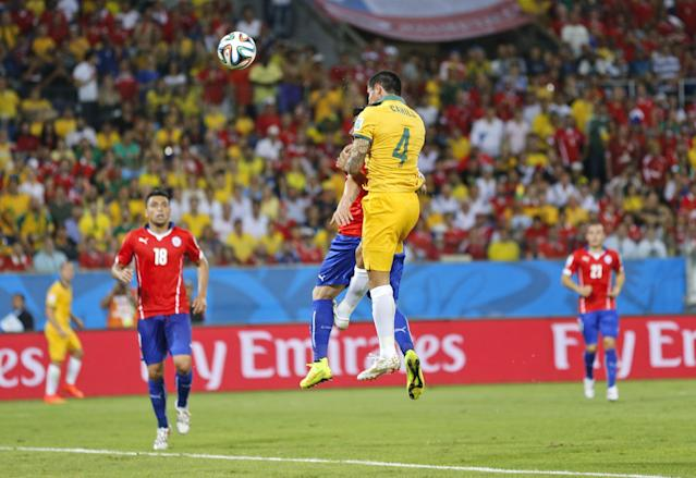 Australia's Tim Cahill, center, scores his side's first goal during the group B World Cup soccer match between Chile and Australia in the Arena Pantanal in Cuiaba, Brazil, Friday, June 13, 2014. (AP Photo/Frank Augstein)