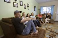 """In this Sept. 11, 2013, photo, Brady Williams talks while his wives, from left to right, Robyn, Paulie, Rosemary, Nonie, and Rhonda, look on during an interview at their home in a polygamous community outside Salt Lake City. Brady Williams has five wives, 24 children but no organized religion. The latest polygamous family from Utah to open its lives to America via reality TV is a tried and true plural family. The kids range from age 2 to 20, and five are named Brady. A one-hour special called """"My Five Wives"""" is set to air Sunday on TLC offering a glimpse into the family's life. (AP Photo/Rick Bowmer)"""