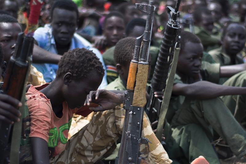 Children soldiers sit with their rifles at a disarmament ceremony in Pibor, South Sudan overseen by UNICEF and partners on February 10, 2015 (AFP Photo/Charles Lomodong)