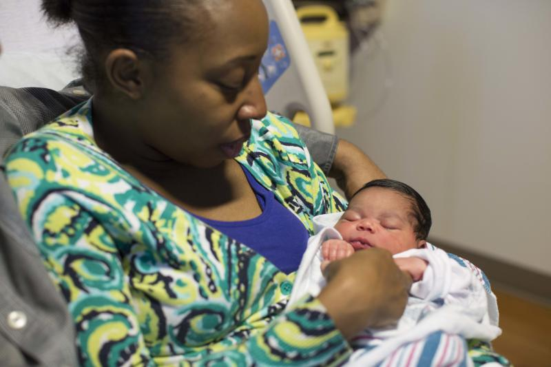 Melissa Jones holds her newborn daughter Mariah Faith Ross in her hospital room at Prentice Women's Hospital in Chicago, Friday, June 7, 2013. Jones couldn't make it inside of the hospital in time Thursday evening, and delivered Mariah in the family's minivan, just feet from the front door of Prentice Women's Hospital. (AP Photo/Scott Eisen)
