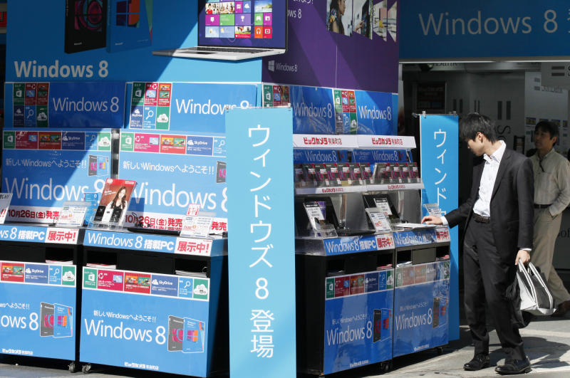 A man checks the Microsoft Windows 8 operation system at a discount electronic store after the launch of the new system in Tokyo Friday, Oct. 26, 2012. The vertical sigh reads: Arrival of Windows 8. (AP Photo/Koji Sasahara)