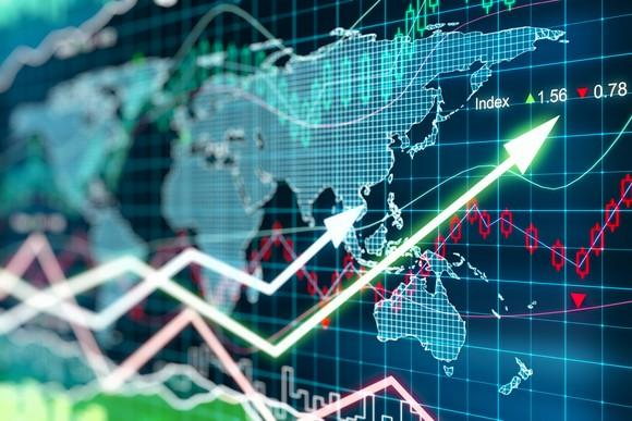 Stock market chart indicating volatility and overlaying a global map on a digital display