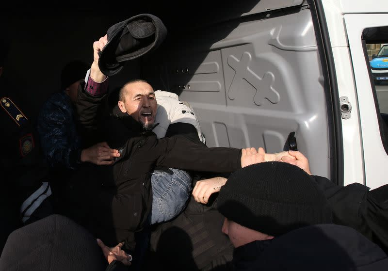 Kazakh law enforcement officers detain a protester during a rally held by opposition supporters in Almaty