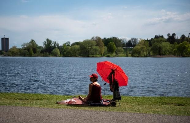A person rests in dark red sits in the shade of their brighter red umbrella on the edge of Dows Lake in Ottawa May 16, 2021. (Justin Tang/Canadian Press - image credit)