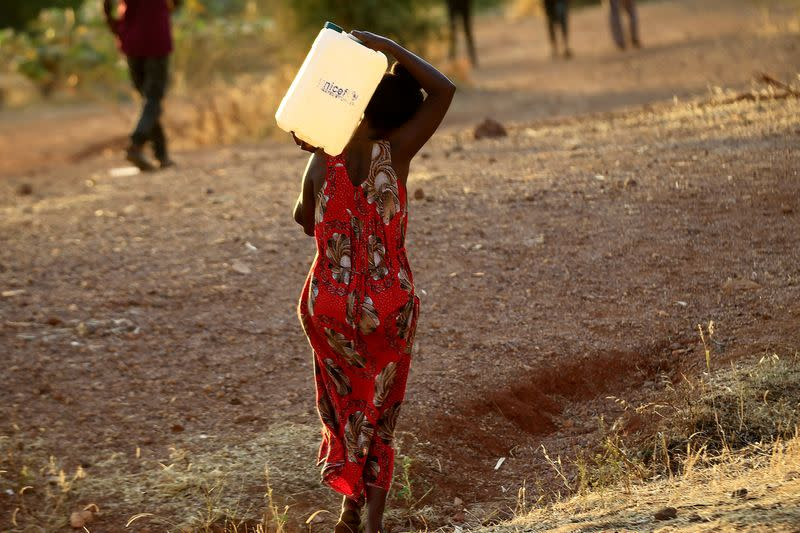 FILE PHOTO: An Ethiopian woman who fled war in Tigray region carries a jerrycan of water as she walks at the Um-Rakoba camp on the Sudan-Ethiopia border in Al-Qadarif state