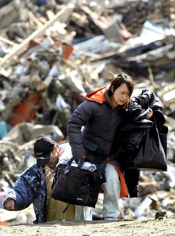 A woman carries belongings she collected from a house swept by a tsunami at Rikuzentakada, northeastern Japan, on Saturday March 12, 2011, one day after a giant quake and tsunami struck the country's northeastern coast. (AP Photo/Kyodo News)