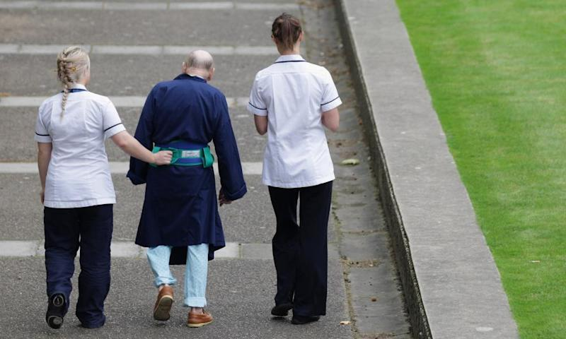 Two NHS staff walk with an elderly patient outside St Thomas' Hospital in London