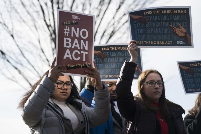 People hold signs in support of ending a ban on travel to the United States