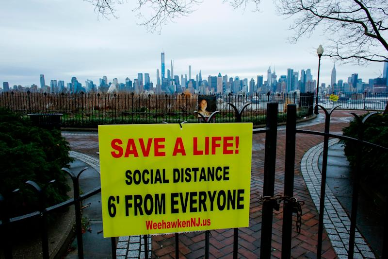 A sign encouraging social distancing to stop the spread of coronavirus is displayed at a closed park in Weehawken, New Jersey, on Saturday. (Photo: KENA BETANCUR via Getty Images)