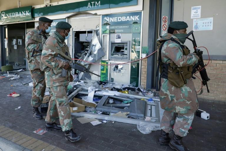 Troops walk past the remains of an automated teller machine (ATM) in the Diepkloof Square mall in Soweto