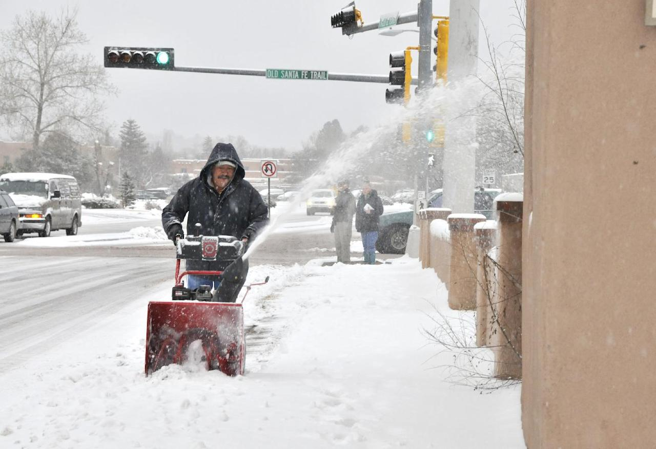 Sidewalks get cleared along the Paseo de Peralta in Santa Fe, N.M. as Santa Fe residents deal with the winter storm that hit Monday Dec. 19, 2011. New Mexico state police say a winter storm is shutting highways and causing difficult driving across northern New Mexico. Los Alamos National Laboratory and a number of schools have closed as the storm moves across New Mexico and into the Texas and Oklahoma Panhandles and parts of Kansas and Colorado. (AP Photo/The New Mexican, Clyde Mueller)