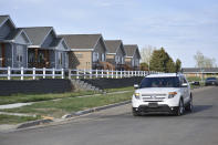 In this Wednesday, May 19, 2021, photo, an SUV drives down a residential street on the Fort Berthold Indian Reservation in Parshall, North Dakota. Oil pumped from Native American lands in the U.S. increased about tenfold since 2009 to more than 130 million barrels annually, bringing new wealth to about a dozen tribes. (AP Photo/Matthew Brown)