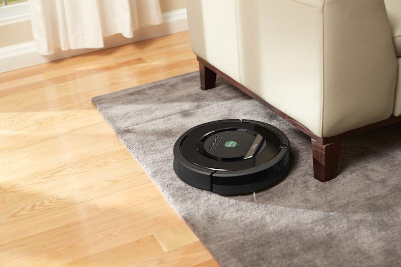 Roomba cleaning a carpet near a couch