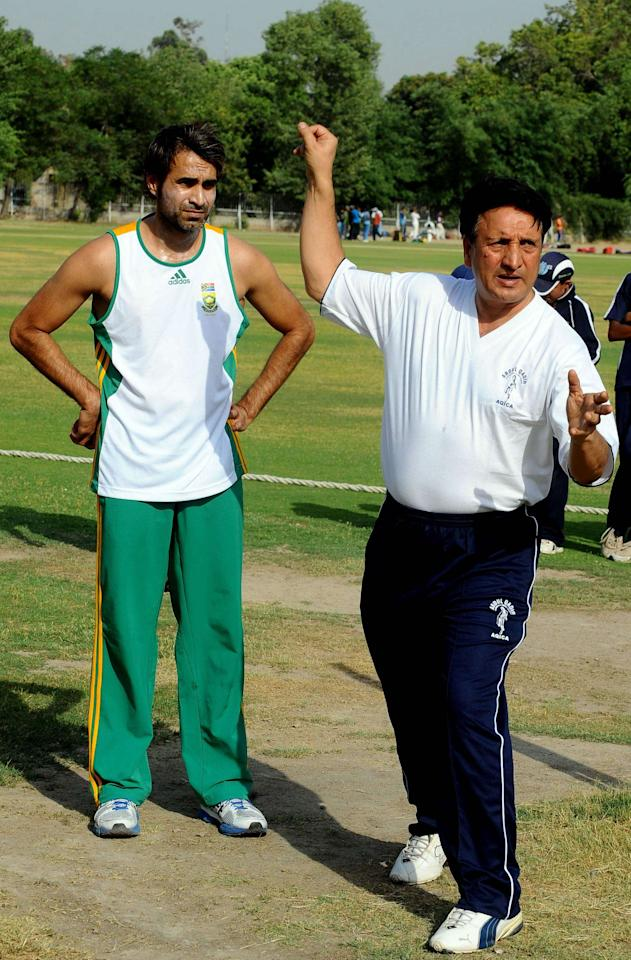 South African leg-spinner Imran Tahir (R) speaks with former Pakistani cricketer Abdul Qadir during a training session in Lahore on May 29, 2012. South African leg-spinner Imran Tahir has returned to his native Pakistan to seek tips from old tutor Abdul Qadir in a bid to exploit England's weakness against spin when the teams meet in July. Tahir, who developed as a spinner in Pakistan before qualifying to play for South Africa last year, arrived last week and trained with Pakistan legend Qadir on Tuesday. Qadir, 56, who was revered as a great leg-spinner during the 70s and 80s, predicted Tahir could play a lead role for South Africa, whose attack is dominated by pace. AFP PHOTO / ARIF ALIArif Ali/AFP/GettyImages