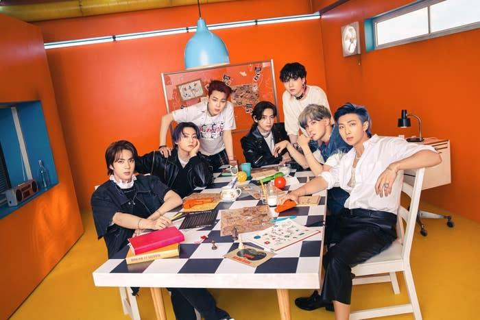 BTS poses while sitting at a table filled with books and games