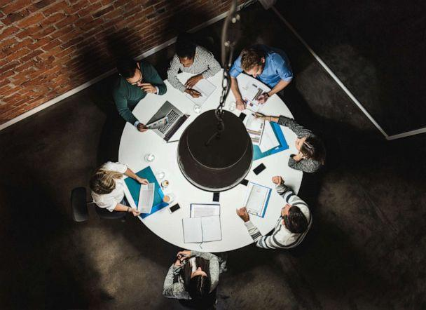 PHOTO: High angle view of large group of business people examining reports while sitting at the table in the office. (Getty Images, FILE)