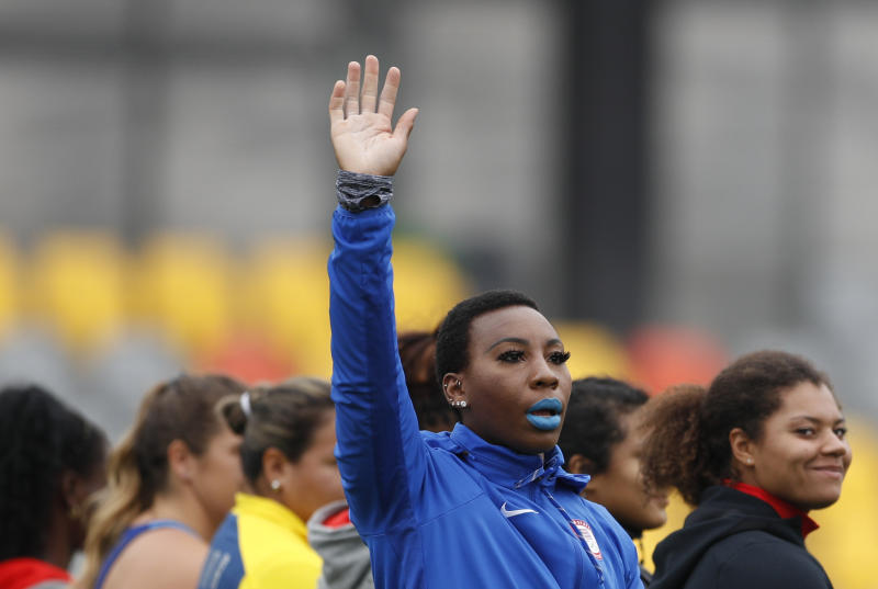 "FILE - In this Aug. 10, 2019, file photo, Gwendolyn ""Gwen"" Berry of the United States waves as she is introduced at the start of the women's hammer throw final, during athletics competition at the Pan American Games in Lima, Peru. Berry won the gold medal. The U.S. Olympic and Paralympic Committee is signaling willingness to challenge longstanding IOC rules restricting protests at the Olympics, while also facing backlash from some of its own athletes for moves viewed by some as not being driven by sufficient athlete input. (AP Photo/Rebecca Blackwell, File)"