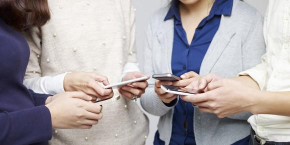 Group of people, shown only from the neck down, using mobile phones
