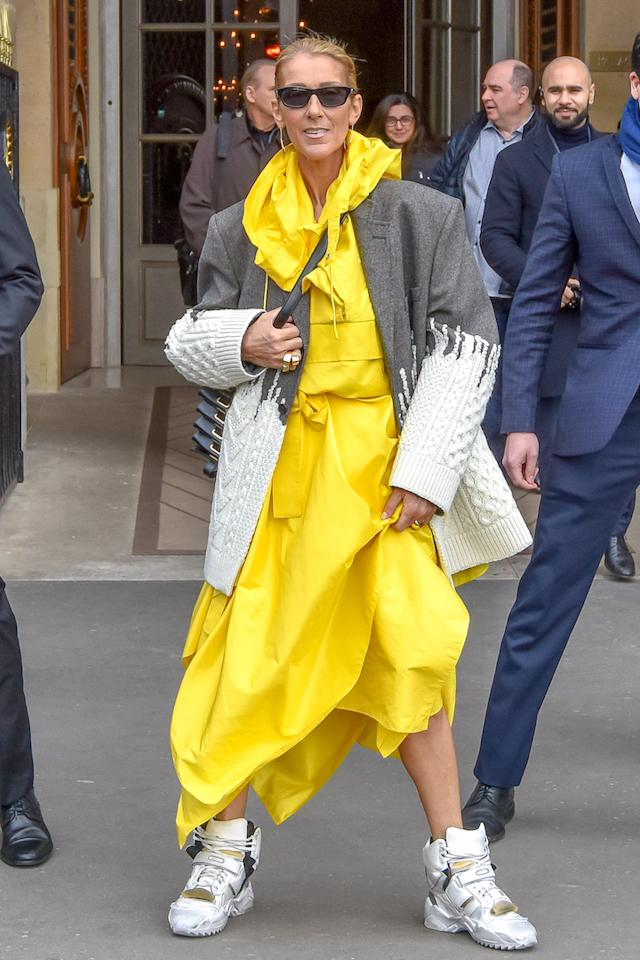 The singer was photographed leaving her hotel in Paris dressed for any unanticipated showers courtesy of a sunny yellow mac and stompy trainers. [Photo: Getty]