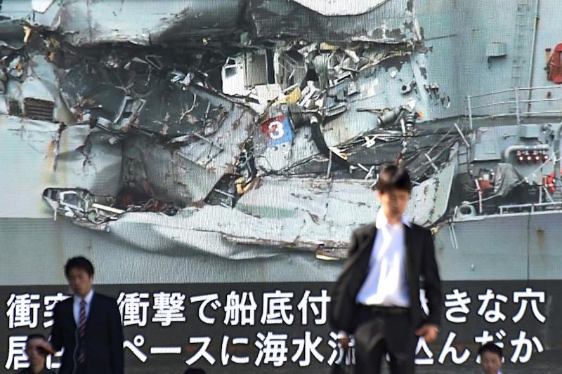 News of the collision between a US warship and a container vessel plays on a huge video screen as a probe into the cause of the crash was under way