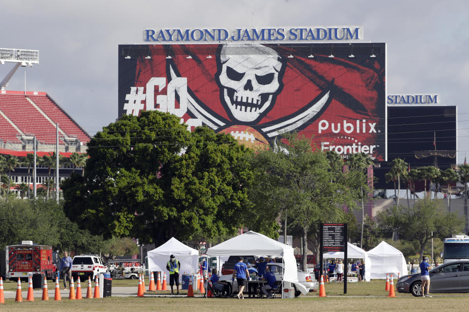 White tents are setup for COVID-19 tests in the parking lot with the Raymond James Stadium sign in the background.